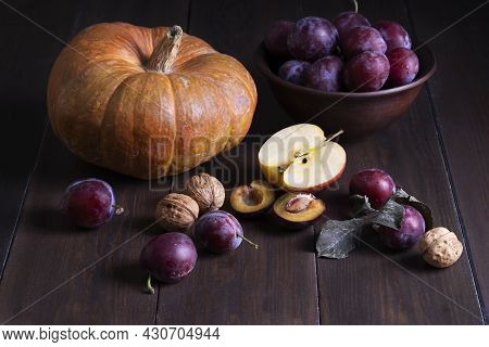 Still Life With Autumn Fruits. Fresh Ripe Plums, Pumpkin, Apple And Walnuts On A Dark Wooden Surface