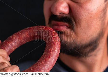 The Man Sniffs A Circle Of Sausage And Winces At The Unpleasant Smell
