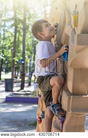 Portrait Of Cute Cheerful Naughty Little Boy Child Plays On Playground. Amusement Park For Kids. Out