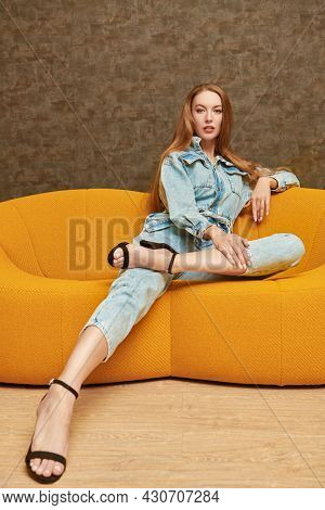 Beautiful fashion model girl poses in denim overalls on a bright yellow sofa in a modern apartment. Fashion shot. Modern interior, furniture.