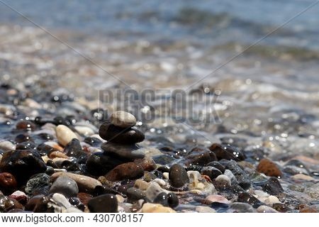 Pebble Stones On Blurred Background Of Sea Waves. Summer Vacation, Stone Tower, Balance And Relax Co