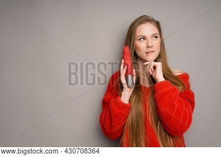 A Beautiful Italian Girl In A Red Sweater Looks Mysteriously Into The Distance And Holds A Vibrator