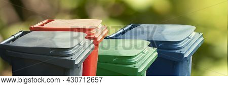 Many Multicolored Trash Bin On Green Nature Background. Separate And Sorting Garbage. Recycling And