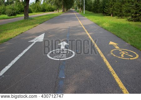 Signs Of Arrow, Bike, Roller Skates And Pedestrian Painted On Pavement In City Park. White And Yello