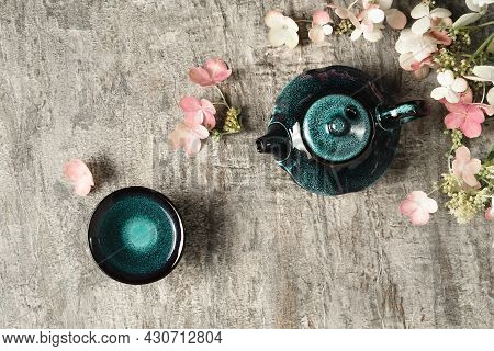 Green Tea In Dark Turquoise Clay Teapot And Small Cup On Grey Wooden Background With Pink And White