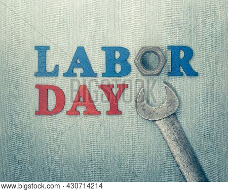 Worn and weathered wrench with Labor Day text, celebrating American workers.