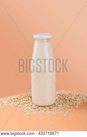 Vegan Non Dairy Alternative Milk. Oat Milk In A Bottle On The Oat Flake On Pastel Peach Terracotta C