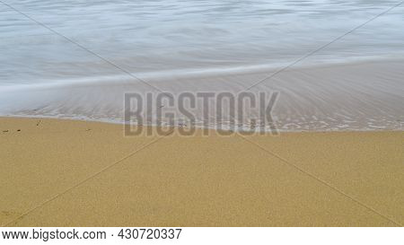 The Smooth Silky Waves And Seafoam On The Sandy Beach, Long Exposure Photograph.