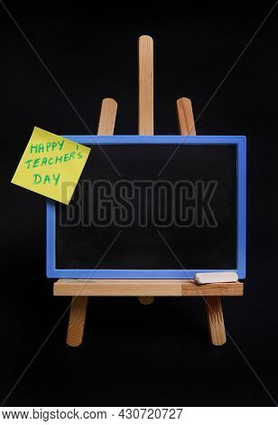 Close-up Of Table Easel With Chalk And Blackboard With Empty Blank Space For Text And Pasted Note Pa