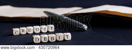 Caption Debit Credit On A Dark Surface Next To A Pen And An Open Notebook. The Concept Of Accounting