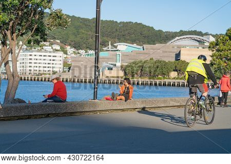 Wellington New Zealand - July 30 2021; People Using Devices Sitting On Edge Relaxing And Cycling Alo