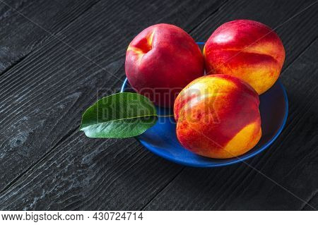 Three Red Ripe Nectarine Hybrids In Their Ripening Season Lie On Blue Plate Or On A Dark Vintage Tab
