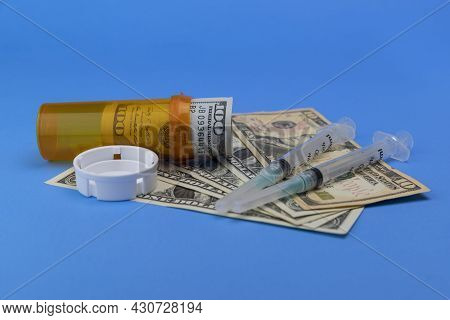 Hundred Dollar Bill And Smaller Dollar Bills With A Pill Bottle And Syringes Representing The High C