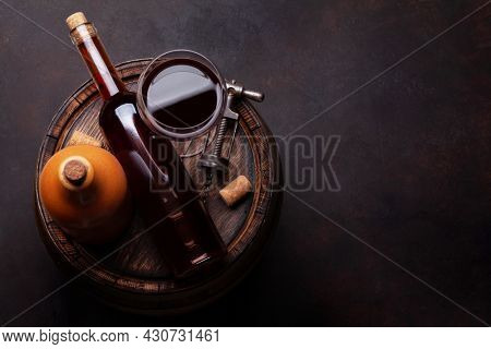 Red wine glass and wine bottles on old wooden barrel. Top view flat lay with copy space