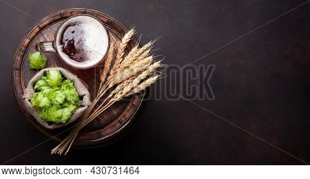 Lager beer mug, hops and wheat on old wooden barrel. Top view flat lay with copy space