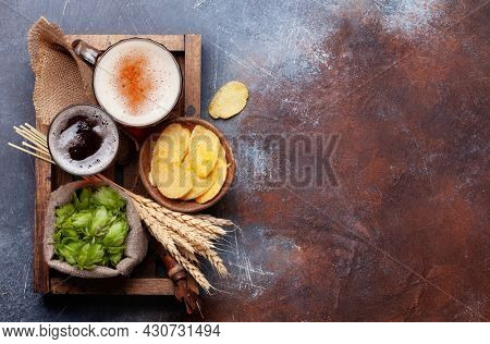 Lager and dark beer mug, hops and wheat on old stone table. Top view flat lay with copy space