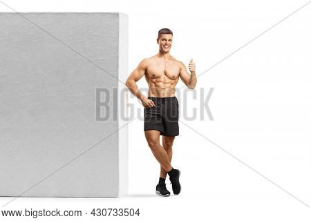 Full length portrait of a bodybuilder leaning shirtless on a wall and showing a thumb up sign isolated on white background