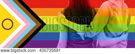 lgbtq, trans and intersex rights concept - close up of female gay couple hugging over rainbow progress pride flag on background