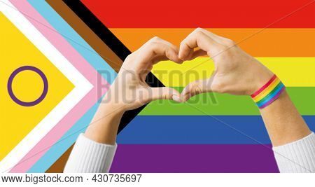 lgbtq, trans and intersex rights concept - close up of couple wearing rainbow ribbon wristbands and showing hand heart over progress pride flag on background