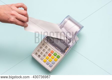 Close-up Of A Hand Holding A Blank White Check On A Cash Register Against A Blue Background, Receipt