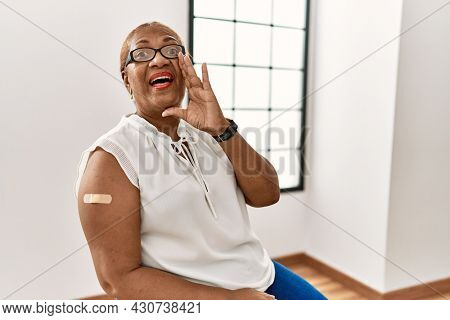 Mature hispanic woman getting vaccine showing arm with band aid shouting and screaming loud to side with hand on mouth. communication concept.