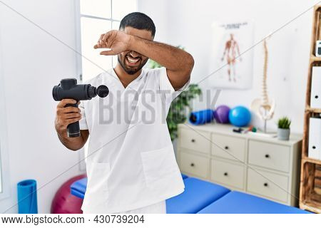 Young indian physiotherapist holding therapy massage gun at wellness center smiling cheerful playing peek a boo with hands showing face. surprised and exited