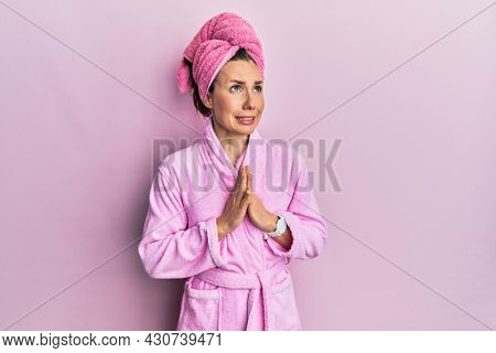 Young blonde woman wearing shower towel cap and bathrobe begging and praying with hands together with hope expression on face very emotional and worried. begging.