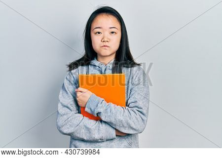 Young chinese girl holding book puffing cheeks with funny face. mouth inflated with air, catching air.
