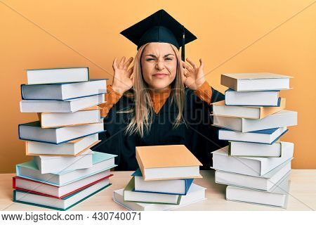 Young caucasian woman wearing graduation ceremony robe sitting on the table trying to hear both hands on ear gesture, curious for gossip. hearing problem, deaf