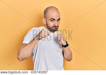 Young bald man wearing casual white t shirt punching fist to fight, aggressive and angry attack, threat and violence