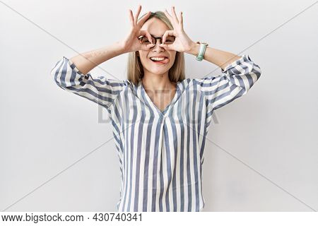 Asian young woman wearing casual clothes and glasses doing ok gesture like binoculars sticking tongue out, eyes looking through fingers. crazy expression.