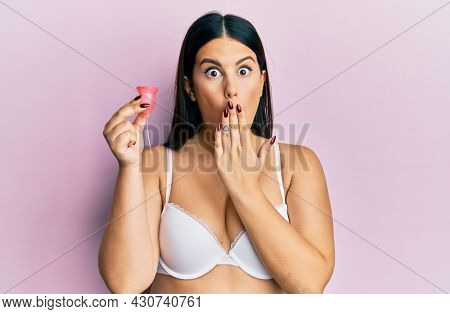 Beautiful brunette woman holding menstrual cup wearing underwear afraid and shocked with surprise and amazed expression, fear and excited face.