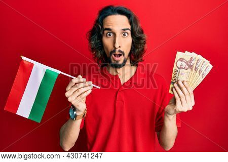 Young hispanic man holding hungary flag and forints afraid and shocked with surprise and amazed expression, fear and excited face.