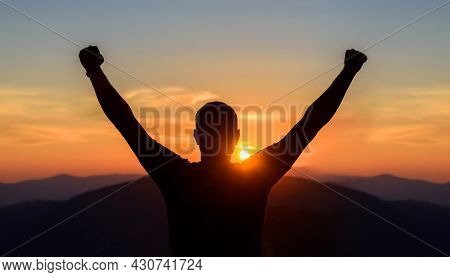 Free Man Raising Arms To Golden Sunset Summer Sky. Freedom, Success And Hope Concept. Boy Relaxing A