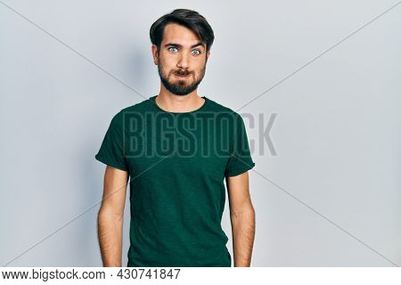 Young hispanic man wearing casual white tshirt puffing cheeks with funny face. mouth inflated with air, crazy expression.
