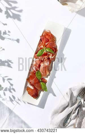 Italian antipasti on white table. Meat starter - sliced meat with basil on white dish. Sunshine and shadow on white table. Traditional italian first course include prosciutto, bresaola and parma ham