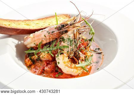 Seafood with tomato sauce on white restaurant plate. Shrimp seafood and tomato stew garnished with fried bread. Isolated on white background