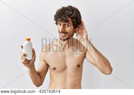 Young hispanic man standing shirtless holding sunscreen lotion smiling with hand over ear listening an hearing to rumor or gossip. deafness concept.