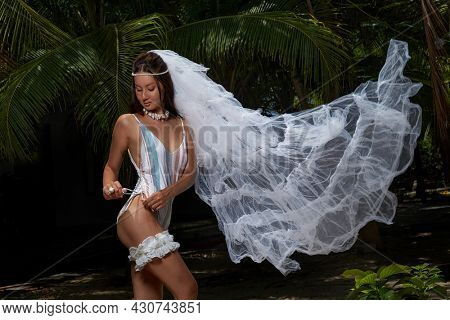 Bride in a light swimming wear with veil and garter surrounded by palm leaves. The inscription