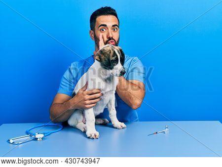 Handsome hispanic veterinary man with beard checking dog health hand on mouth telling secret rumor, whispering malicious talk conversation