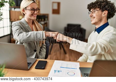 Two business executives hitting fists at the office.