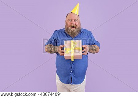 Excited Plump Man Wearing Tight Shirt Holds Present On Purple Background