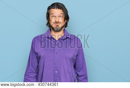 Middle age handsome man wearing business shirt puffing cheeks with funny face. mouth inflated with air, crazy expression.