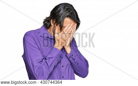 Middle age handsome man wearing business shirt with sad expression covering face with hands while crying. depression concept.