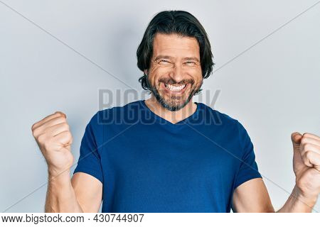 Middle age caucasian man wearing casual clothes very happy and excited doing winner gesture with arms raised, smiling and screaming for success. celebration concept.