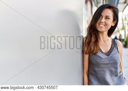 Beautiful caucasian woman looking elegant and happy leaning on a wall outdoors on a sunny day