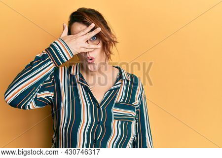 Young caucasian woman wearing casual clothes and glasses peeking in shock covering face and eyes with hand, looking through fingers with embarrassed expression.