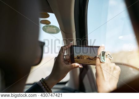 Asian Female Tourist Taking A Photo Using Cellphone While Traveling By Car