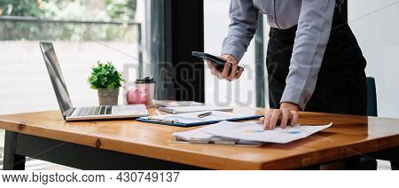 Business Woman Discussing On Stockmarket Charts In Office, Working On Smart Phone And Laptop Compute
