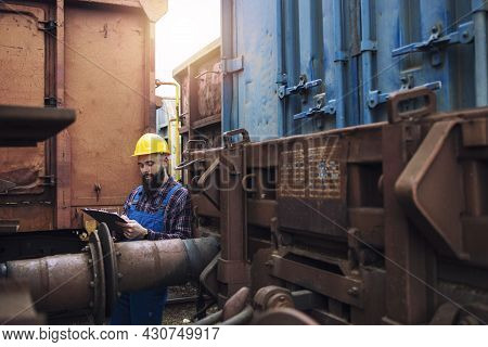 Train Maintenance Railroad Worker Checking Wagons And Cars Before Departure.